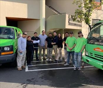 This is 10 of our team members standing next to work vans in front of a commercial building.